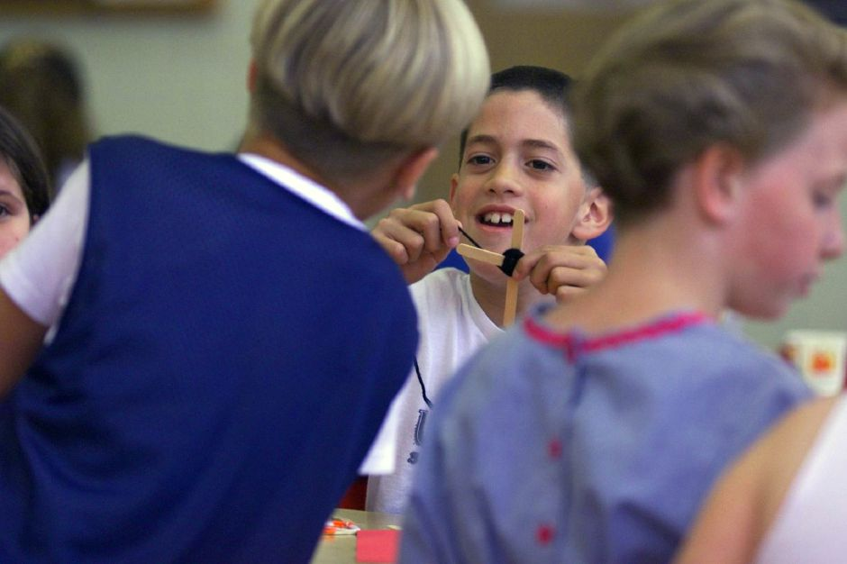 "Jon Amenta, 8 , a 3rd grader at Derynoski Elementary School talks to a friend, Mike Stokes, 8, while making an ""Ojo de Dios"" or God"