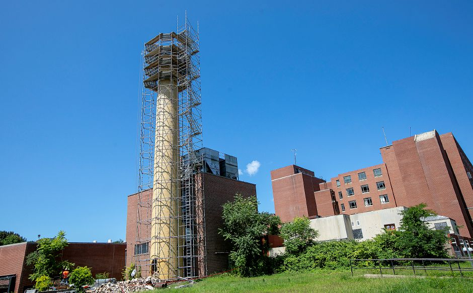 Crews from West Hartford based Advanced Scaffold Services dismantle the smokestack of the former Meriden-Wallingford Hospital on Cook Avenue in Meriden, Thursday, August 23, 2018. Dave Zajac, Record-Journal