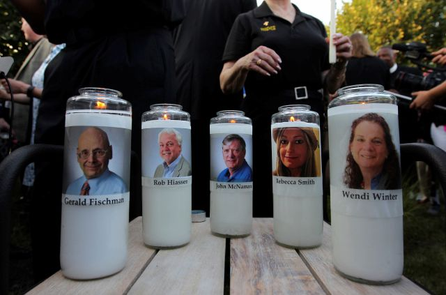 Photos of five journalists adorn candles during a vigil across the street from where they  were slain in their newsroom in Annapolis, Md., Friday, June 29, 2018. Prosecutors say Jarrod W. Ramos opened fire Thursday in the Capital Gazette newsroom. (AP Photo/Jose Luis Magana)