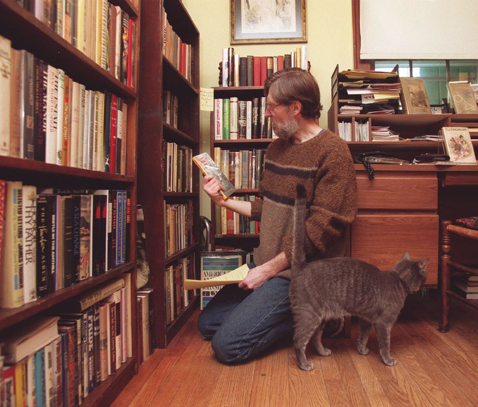 RJ file photo - Stephen Lupack of Meriden looks through a list of rare books that will be on his January sale list. Lupack is a rare book dealer. His cat is named Caliban, Jan. 1999.