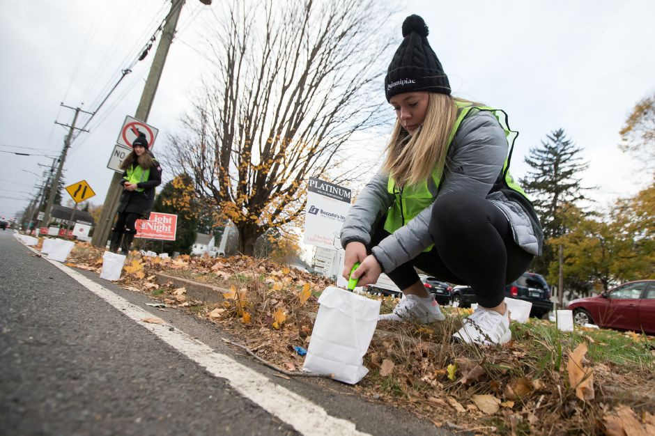 Casey Oppenheimer 15 of Cheshire lights a luminary on Route 10 Saturday during the 14th Annual Cheshire Lights of Hope to raise money for local charities in Cheshire November 10, 2018 | Justin Weekes / Special to the Record-Journal