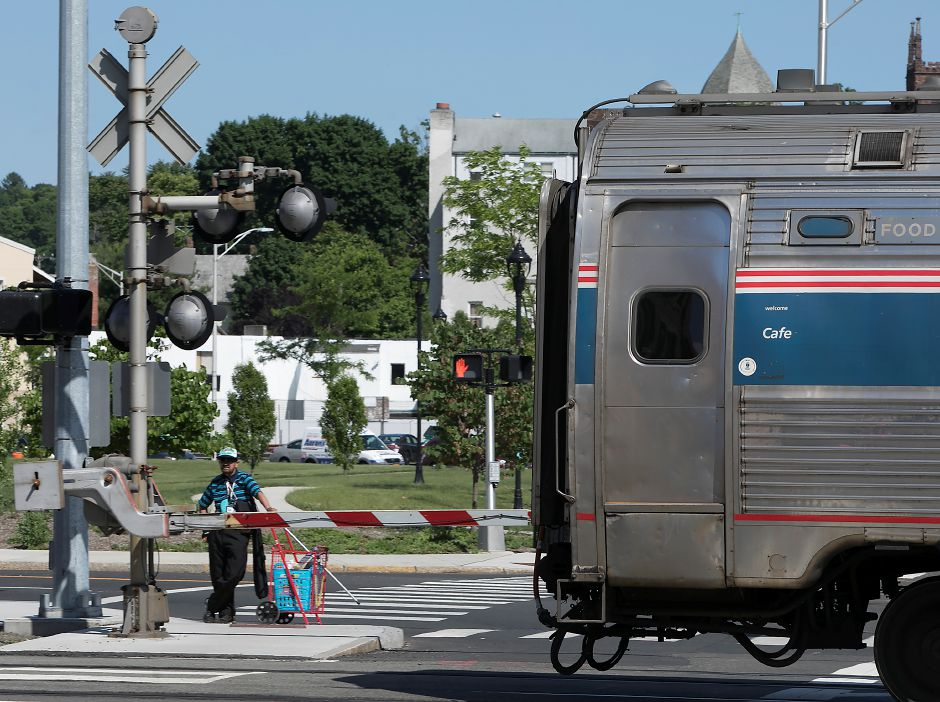A man waits at the gate for an Amtrak train to pass in downtown Meriden, Monday, June 11, 2018.  Dave Zajac, Record-Journal