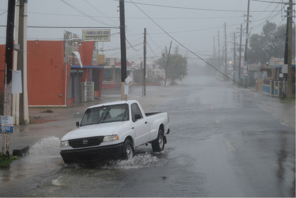 A man drives through rain and strong winds during the passage of hurricane Irma, in Fajardo, Puerto Rico, Wednesday, Sept. 6, 2017. The US territory was first to declare a state of emergency las Monday, as the National Hurricane Center forecast that the storm would strike the Island Wednesday. (AP Photo/Carlos Giusti)