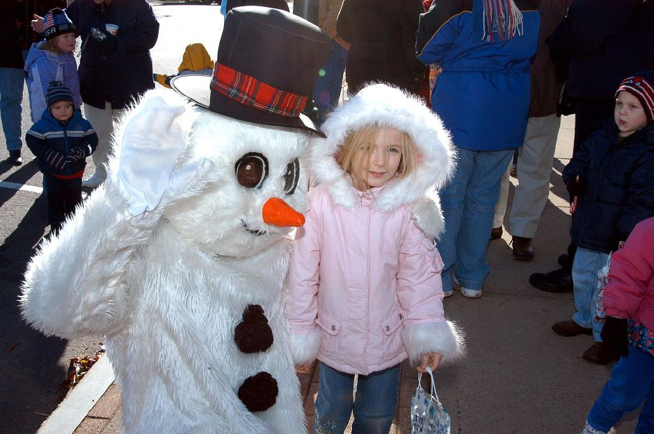 Frosty the Snowman says hello to five-year-old Lindsey Kelleher during the holiday festiviities at the Christmas Festival held Saturday, Dec. 3 in Wallingford.