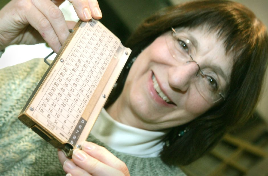 Karen Roesler, a co-director of the Wallingford Public Library, holds an old device used to calculate fines due on late material. Black little square numbers would slide into a groove and become aligned with the correct amount owed based on what day it was. This is one of the items found in the library as they are adding on to the building. Chris Angileri/Record-Journal.