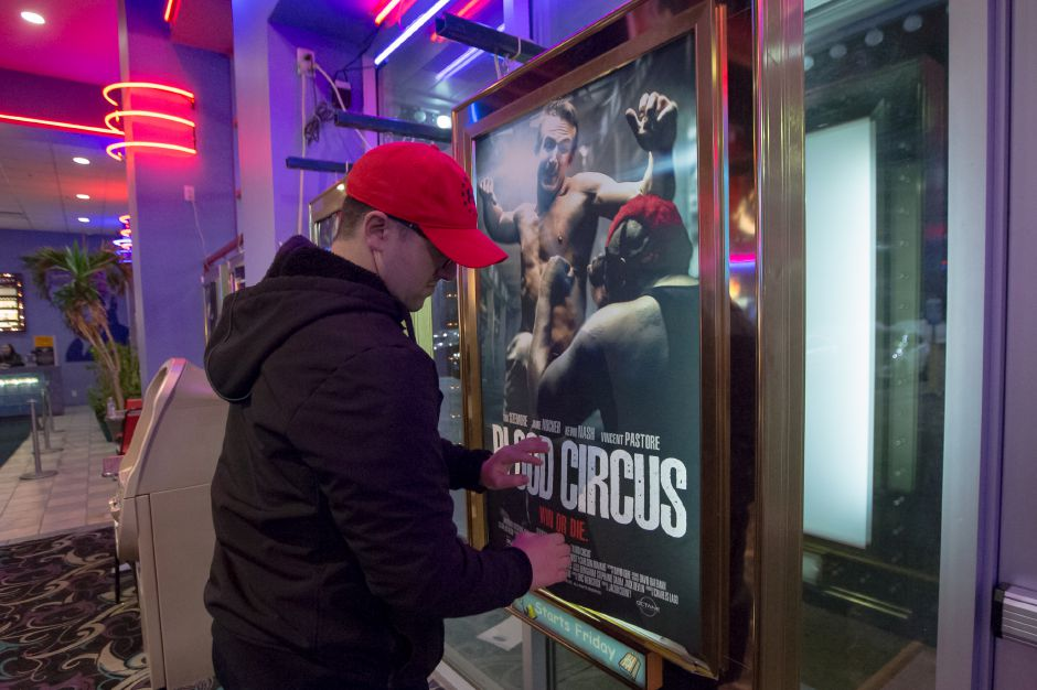"Mathew Morin who plays a CSI in the film hangs the movie poster Thursday during a premiere of ""Blood Circus"" at Holiday Theaters in Wallingford. Scenes in the movie were filmed at different locations around Connecticut, including Meriden, Middletown and Portland. January 11, 2018 