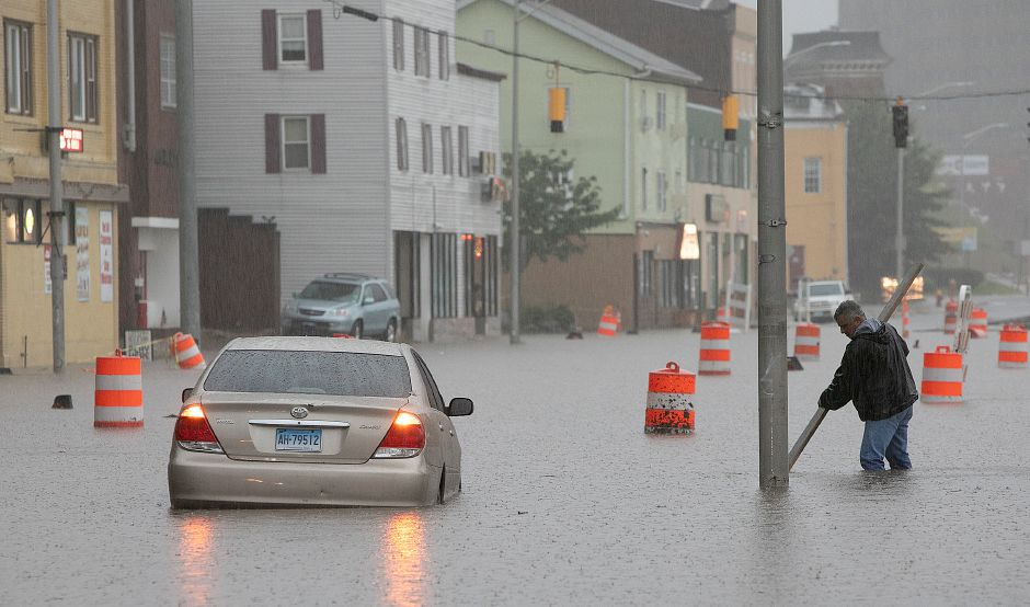 Joe LaRosa, of LaRosa Construction, unclogs storm drains next to a stranded vehicle on Pratt Street in Meriden on Tuesday. Heavy rain Tuesday evening closed roads and flooded basements of local homes. Dave Zajac, Record-Journal