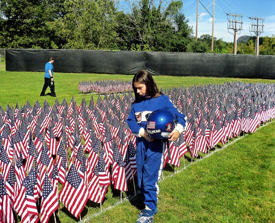 Racecar driver Brianna Oslander,11, walks past a September 11th memorial at the baseball field at the American Legion Post in Meriden, September 11, 2011. In honor of Veteran