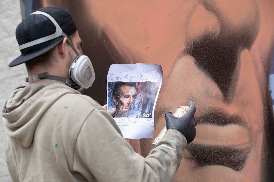 "Global graffiti artist ""ARCY,"" of North Haven, works from a picture while painting a portrait of Abraham Lincoln on an 8-foot-by-12-foot canvas outside Lincoln Middle School in Meriden, Mon., Dec. 3, 2018. ARCY is known for large scale art he creates all over the world, and for organizations like Major League Baseball, Disney and the National Parks Service. Dave Zajac, Record-Journal"