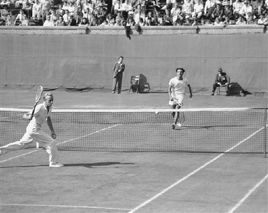Alejo Russell (far court), mustached Argentine tennis star, breaks into a broad smile as he smashes ball out of the reach of Sidney Wood, Jr. (left), of New York, to win a point in their match in the men