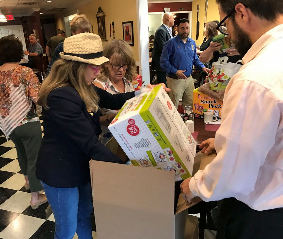 North Haven Rotary President Mary Minotti and Rotarian Donna Mae Cangiano pack boxes of snacks for the Ronald McDonald House.