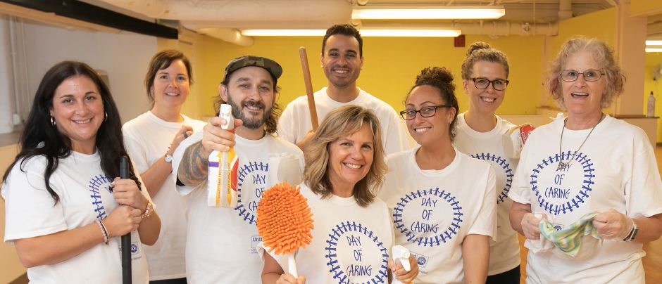 Employees of Wallingford based The Marlin Company are all smiles after cleaning up rooms at the Women and Families Center in Meriden during the United Way