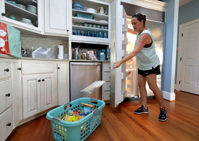 Michelle Stober, of Cary, N.C., removes food from a freezer as she prepares their vacation home in advance of Hurricane Florence in Wrightsville Beach, N.C., Tuesday, Sept. 11, 2018. Florence exploded into a potentially catastrophic hurricane Monday as it closed in on North and South Carolina, carrying winds up to 140 mph (220 kph) and water that could wreak havoc over a wide stretch of the eastern United States later this week. (AP Photo/Chuck Burton)