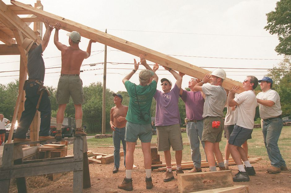 RJ file photo - Ten men list a beam and slide it to the top of a barn-style home addition on Williams Road in Wallingford, Aug. 29, 1998.