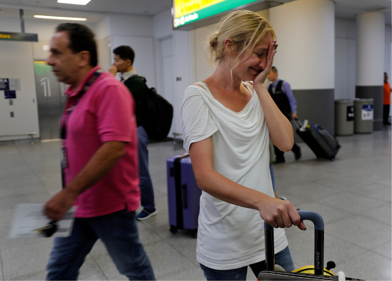 Cori Rojas, a school teacher from Puerto Rico, reacts after arriving at JFK airport with her two children, Tuesday, Sept. 26, 2017 in New York. Rojas and her children fled Puerto Rico after Hurricane Maria devastated the island and will stay with her in-laws in Queens. Her husband, who works for a global insurance firm, opted to stay behind. (AP Photo/Julie Jacobson)
