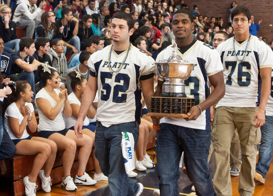 Football team captains Brandon Crespo, left, and Lazarick Hogan, right, carring the Stoddard Bowl, lead the football team into the gym in front of cheering classmates during the pep rally at Platt High School in Meriden, Nov. 21, 2012. (Christopher Zajac / Record-Journal)