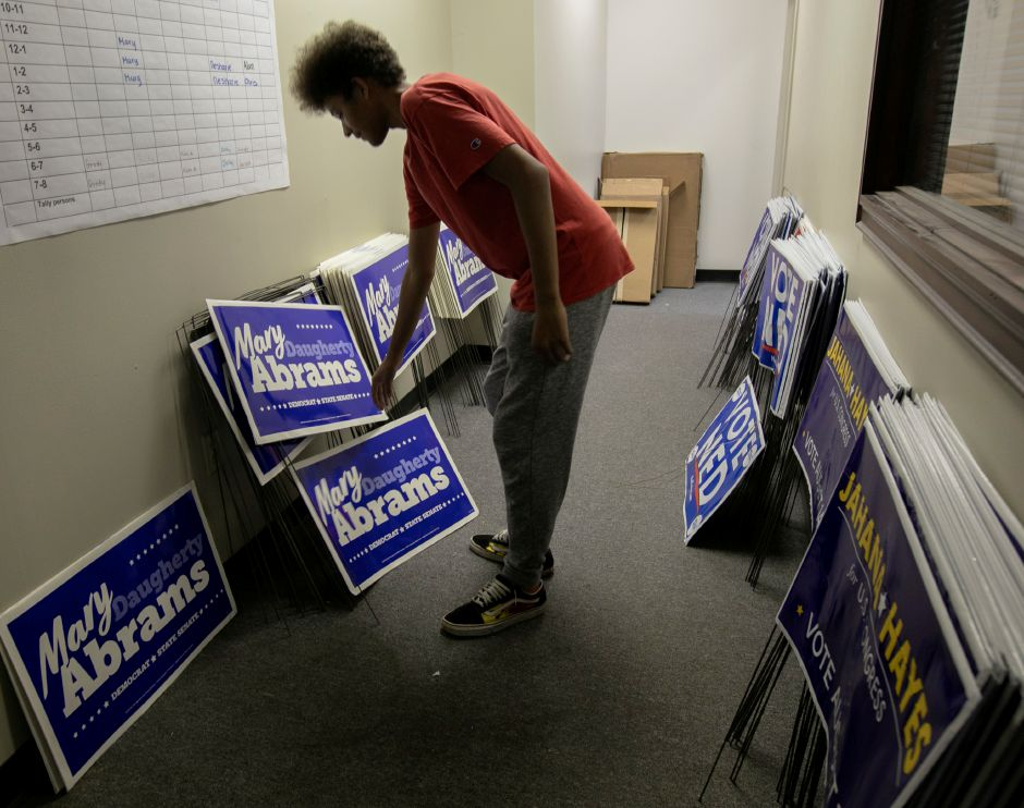 Volunteer pollstander Juan Fermaint, 15, sets down campaign signs upon returning to the campaign headquarters for Mary Daughtery Abrams at 5 Colony St. in Meriden, Tuesday, August 14, 2018. Dave Zajac, Record-Journal