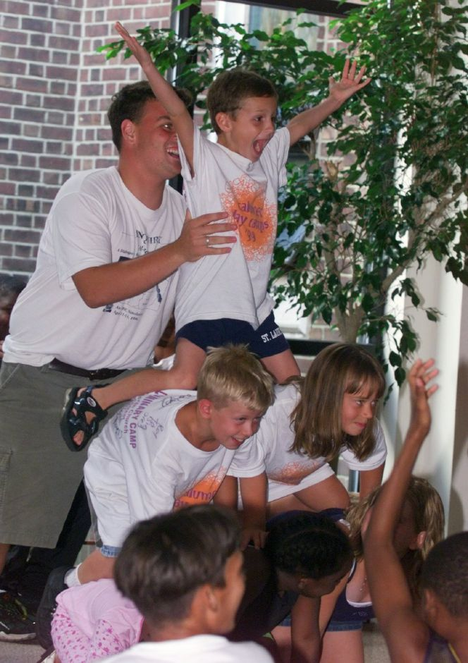 Garrett Maynard, 7, is on top of a human pyramid as councilor Nick McCready holds on Fri., July 23 during Immanuel Lutheran Church