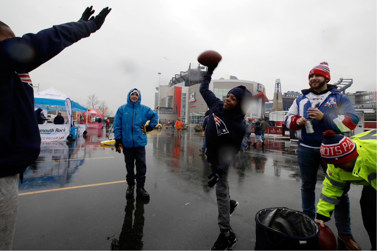 Samir Princeton, of Albany, N.Y., tosses the football while tailgating with friends in the parking lot of Gillette Stadium before an NFL football game between the New England Patriots and the New York Jets, Saturday, Dec. 24, 2016, in Foxborough, Mass. (AP Photo/Charles Krupa)