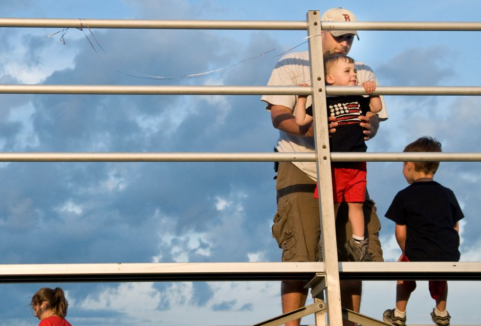 North Haven resident Chris Parker helps his son Colby,2, climb the bleachers as they wait for the fireworks at Sheehan High School in Wallingford, July 2, 2011. (Sarah Nathan/Record-Journal)