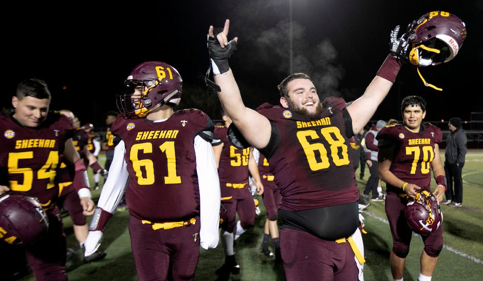The Sheehan Titans, including starting offensive linemen William Seay (68) and Miguel Pinos (70) celebrate after defeating Wolcott 43-20 in the CIAC Class M quarterfinals at Riccitelli Field on Tuesday night. | Dave Zajac, Record-Journal