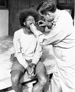Despite a background of black magic and witchcraft, a native Melanesian in New Caledonia eagerly submits to treatment by U.S. Army surgeon stationed on the southwest Pacific island on Sept. 10, 1942. (AP Photo)