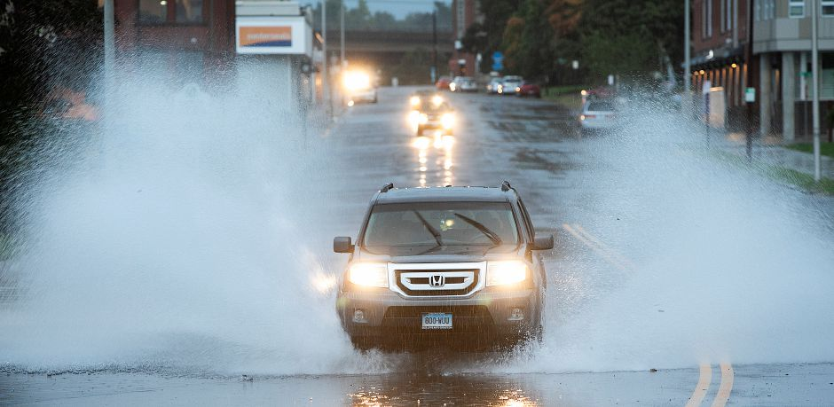 A vehicle blasts through flood waters on State Street in Meriden, Tuesday, Sept. 25, 2018. Heavy rain Tuesday evening closed roads and flooded basements of local homes. Dave Zajac, Record-Journal