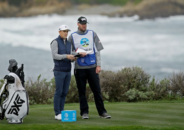 Scott Langley, left, confers with his caddie as he prepares to hit from the fourth tee of the Spyglass Hill Golf Course during the second round of the AT&T Pebble Beach National Pro-Am golf tournament Friday, Feb. 8, 2019, in Pebble Beach, Calif. (AP Photo/Eric Risberg)