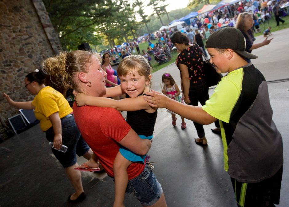 Mikayla Robinson, 4, holds on while dancing with mother Jennifer Byrnes and big brother Tyler Paquet, 10, during the 10th annual celebration of National Night Out at Hubbard Park in Meriden, Tuesday, August 5, 2014. The event is organized by the council of neighborhoods and the Police Department. It is a local offshoot of America's Night Out Against Crime, which began in 1984. | Dave Zajac / Record-Journal