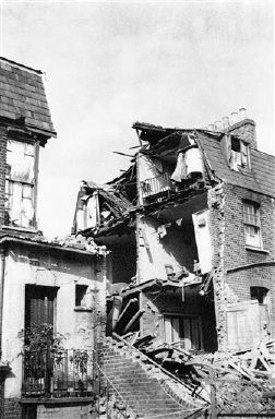 A house in the London area blasted by a German air bomb on August 29, 1940. Note how wall was ?pulled? away, revealing the cross section of the house, the baby crib and clothes in a closet almost undisturbed. (AP Photo)