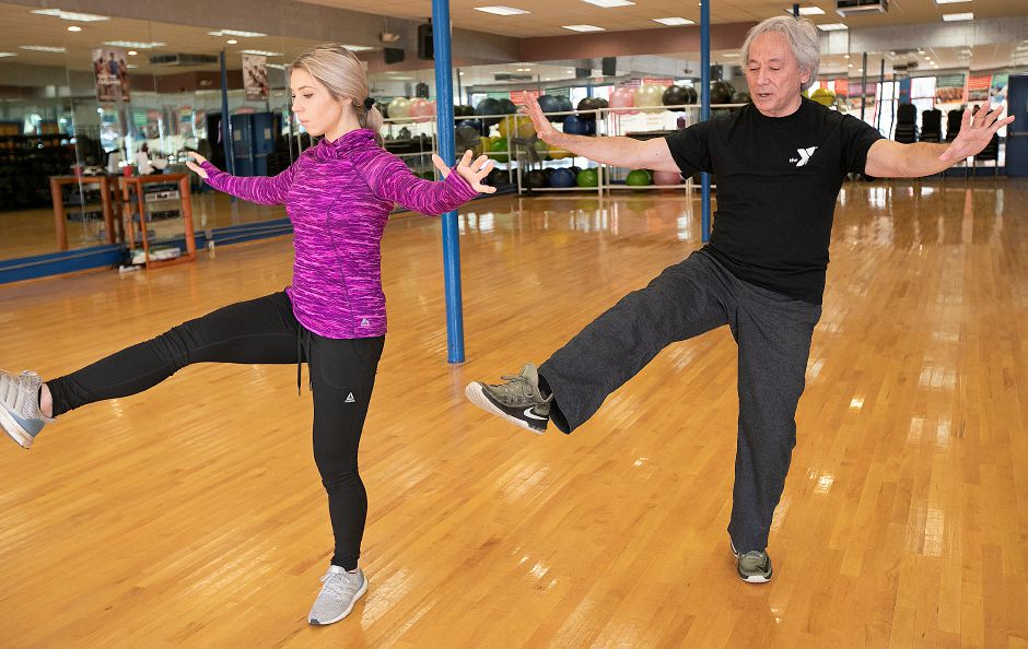 Above: Tai chi instructor George Donahue, of Meriden, works with Kristen Dearborn at the Wallingford YMCA on Friday. Below: Donahue demonstrates different tai chi movements. Photos by Dave Zajac, Record-Journal