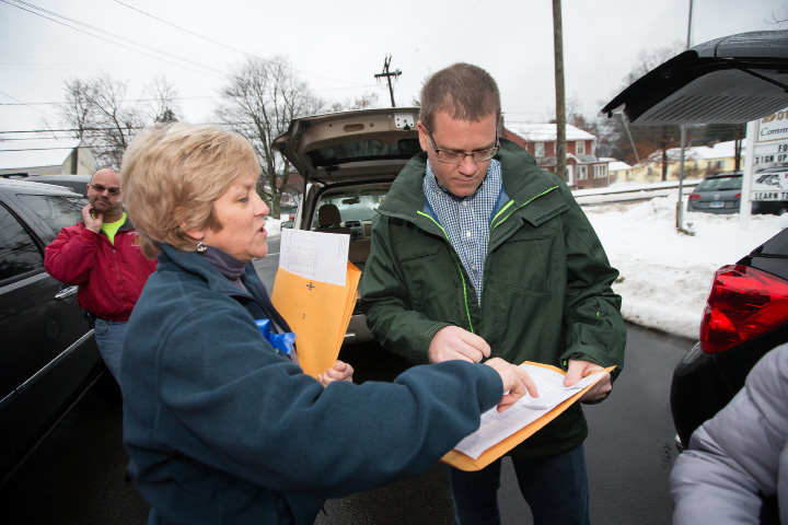 Christine Shanley-Buck and Jim Richard review the delivery route for families receiving food Sunday.| Photos by Justin Weekes, Special to the Record-Journal