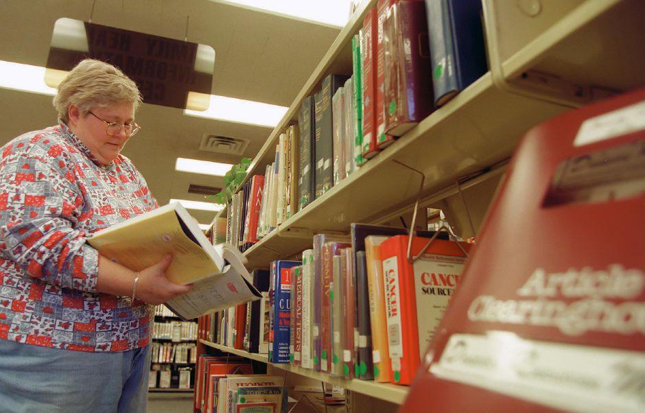 RJ file photo - Debra Thornton, of Meriden, looks through reference books at Meriden Public Library while working on a report on causes and control of infectious diseases, Jan. 1999.