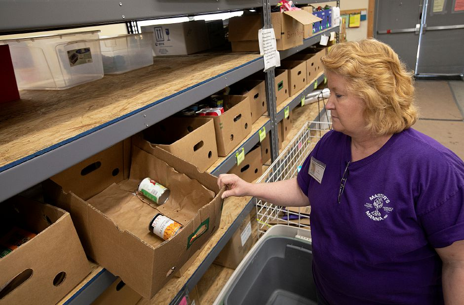 Sue Heald, food pantry manager, looks into a box containing only a few food donated items at Master's Manna, 428 S. Cherry St., in Wallingford on Tuesday. Some local food pantries and food banks are experiencing a shortage of food as donations decline in the summer months. Photos by Dave Zajac, Record-Journal