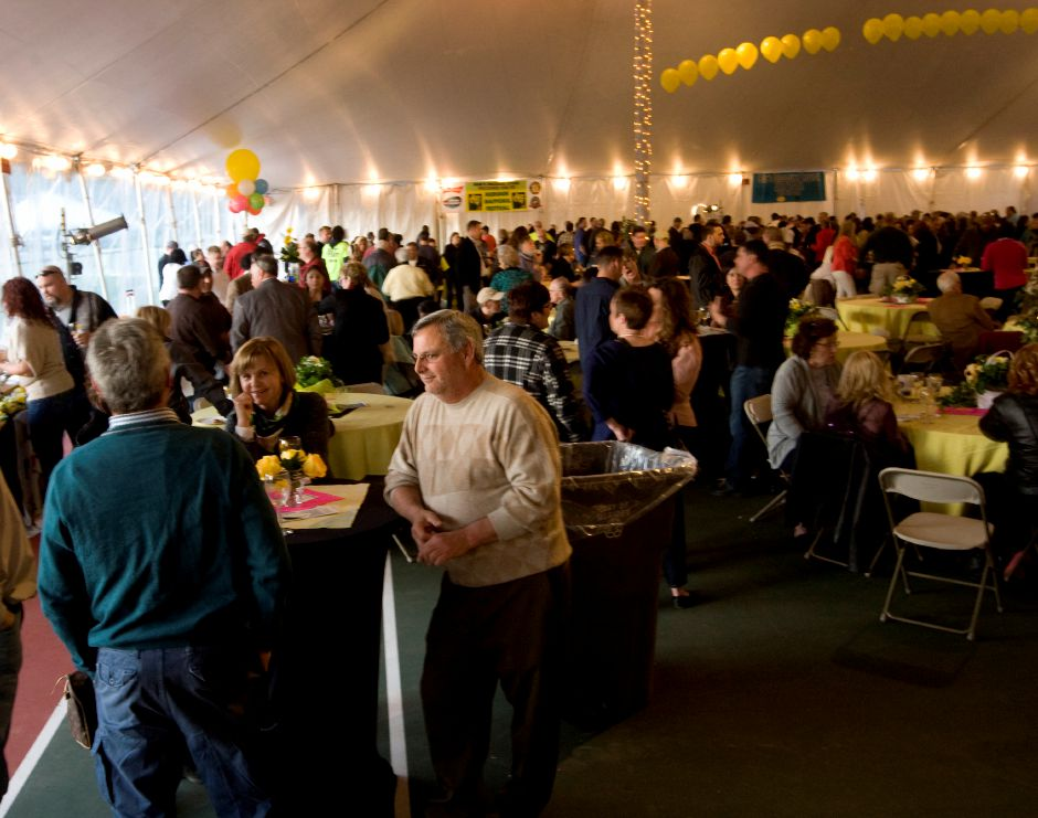 A large crowd gathers under the tent on the tennis courts during the annual Daffodil Festival sponsors and guests dinner, Thursday, April 24, 2014 at Hubbard Park in Meriden. | Dave Zajac / Record-Journal