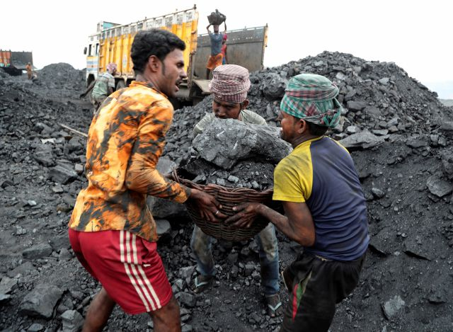 FILE - In this Oct. 23, 2019 file photo, laborers lift a large basket filled with coal before loading it into a truck for transportation in the village of Godhar in Jharia, a remote corner of eastern Jharkhand state, India. (AP Photo/Aijaz Rahi, FILE)
