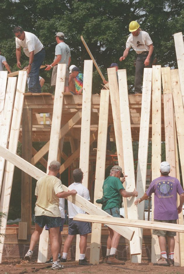 RJ file photo - Tongue-and-groove floor boards are handed up and slid into place, Aug. 29, 1998.