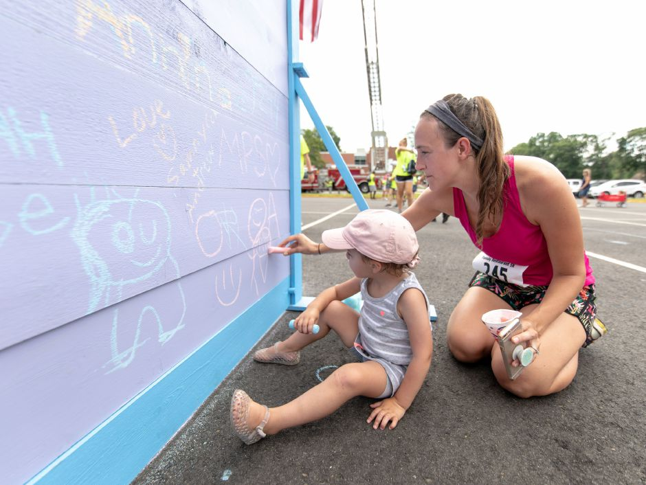 Lauren Mascolo, of West Hartford, helps Andie Mascolo draw on a wall at the Chips Family Restaurant Road Race on July 21, 2019 in Plainville. The run is one of the two largest fundraisers for the Petit Family Foundation, which gives out scholarships for local high school graduates and grants for nonprofits. | Devin Leith-Yessian/Plainville Citizen