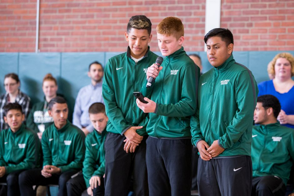 Flanked by their teammates, Maloney soccer players Denis Blandon, Devin Juan and Gustavo Pluma-Sanchez thank fans and classmates for their support during a school pep rally on the eve of the CIAC Class L state championship game. The Spartans were the first Meriden soccer team to reach a state championship game and their dramatic run to the finals, which included a pair of victories in penalty kicks, ranks No. 1 for local sports stories in 2018. | Justin Weekes / Special to the Record-Journal