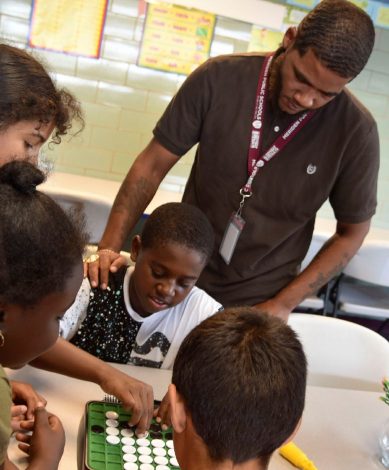 Boys & Girls Club mentor Henry Rhodes, 25, of Meriden, helps students play Othello at the club on Wednesday, Sept. 19. The club is looking to expand its mentorship program. | Bailey Wright, Record-Journal