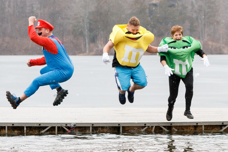 Jerry Brick of Southington Mike Cordan of Southington and Barbara Parlee of Bristol jump into Slopers Pond at the YMCA