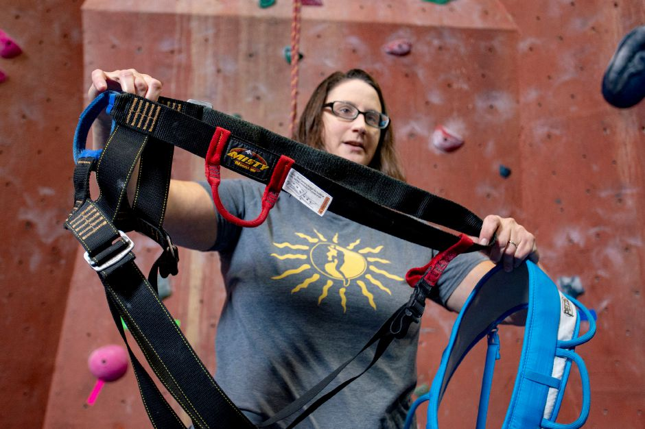 Kristina Godfrey, manager of Prime Climb indoor rock climbing in Wallingford, shows off a couple of the harnesses used in rock climbing Aug. 20, 2018. | Richie Rathsack, Record-Journal