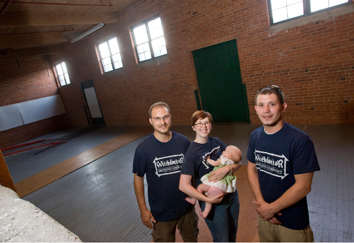 Allison Norris, center, holds 3-month-old daughter, Jocelyn, next to husband, Josh, left, and friend, Daryl Adamaitis, right, at the future home of Witchdoctor Brewing Company in Factory Square on Center Street in Southington, Tuesday, September 8, 2015. The three owners plan to open a brewery and tap room there in the spring.  |  Dave Zajac / Record-Journal