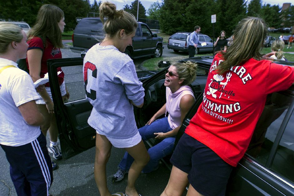 Seated in her car, Cheshire High School senior Kim Fiore,17 shares a laugh with fellow senior swim team members who were waiting in school parking lot to pick up swim team underclassmen for their swim practice Monday afternoon Aug. 30, 1999. Monday was the first day of classes for the school
