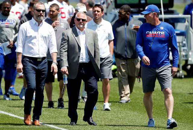 New York Giants head coach Pat Shurmur, right, walks off the field assistant general nanager Kevin Abrams, left, and senior vice president, communications Pat Hanlon after the team