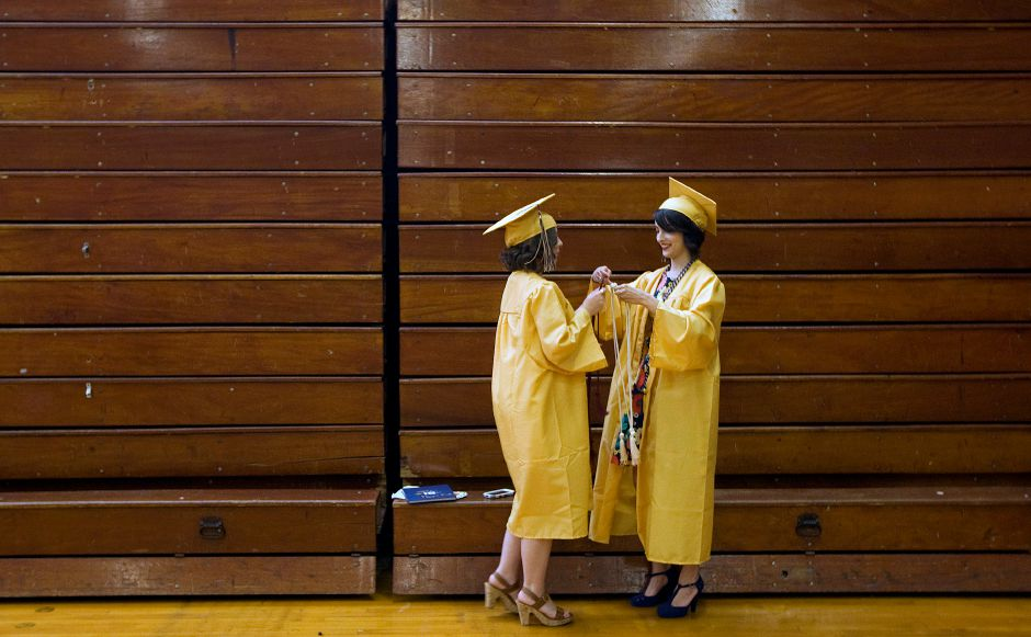 Jillian Russo, 17, left, helps friend, Aubrie Curcio, 18, with her honor cords before the start of graduation ceremonies at Platt High School, Thursday, June 9, 2016. | Dave Zajac, Record-Journal