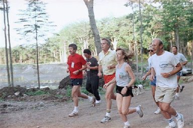 U.S. President George H. Bush, third from left, is joined on a morning jog by a group of reporters as he runs near his home in Kennebunkport, Maine,, Tuesday, August 22, 1989. The president is opening a three-week vacation at his Oceanside home. (AP Photo/Pat Wellenbach)