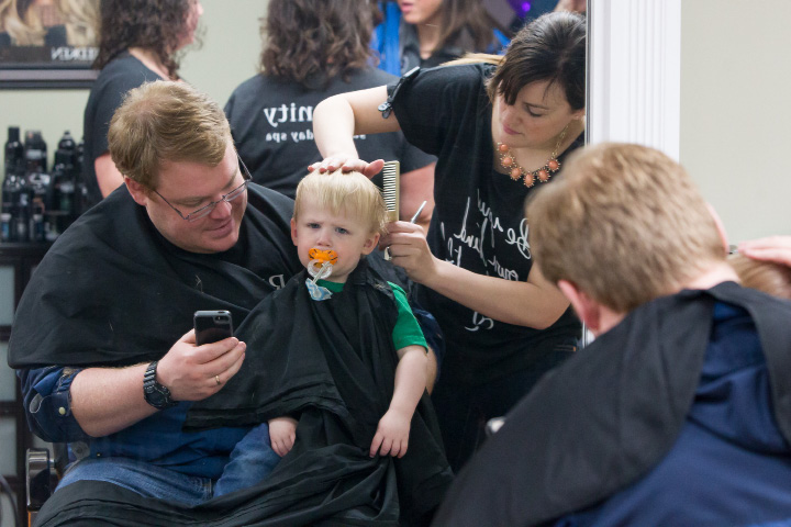 Matt Turner hold his son Grayson 3 as Katie Mitchell give him a trim Sunday during a Cut-A-Thon fund raiser for Wallingford