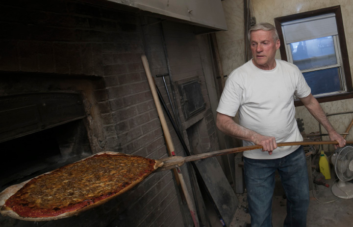 Longtime pizza maker Paul Bernier removes a fresh sausage pie from the brick oven at The Little Rendezvous pizza restaurant on Pratt Street in Meriden, Wednesday, March 22, 2017. Bernier will work his final shift at the pizzeria this weekend. | Dave Zajac, Record-Journal