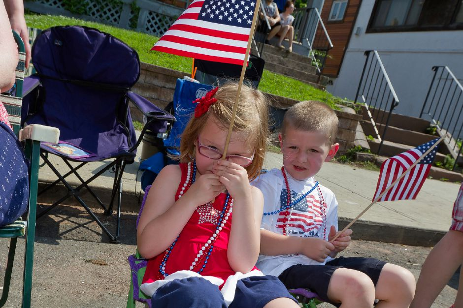 From left: Southington residents Madeline Stair and her twin brother Matthew, 5, wave flags from the sidelines at the Memorial Day Parade in downtown Meriden, May 28, 2012. (Justin Weekes/Record-Journal)